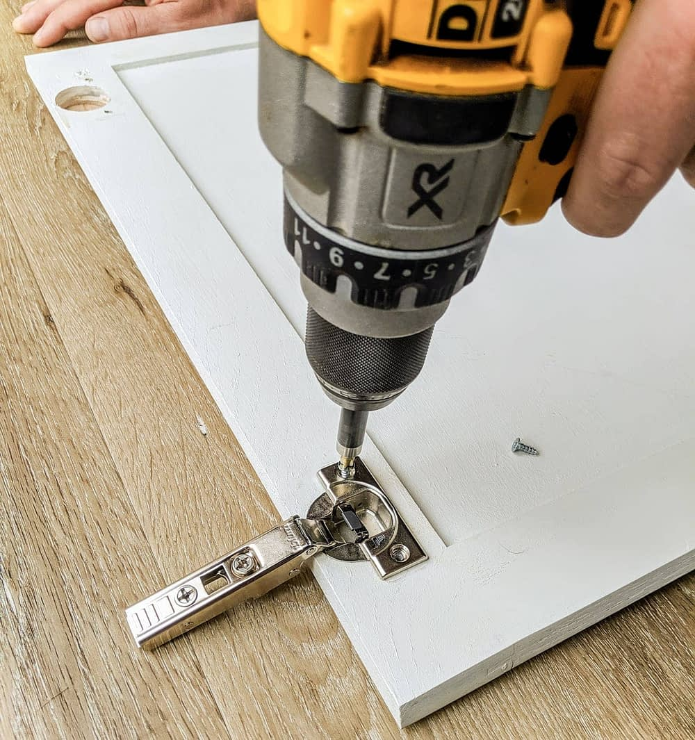 screwing a soft close hinge into a cabinet door