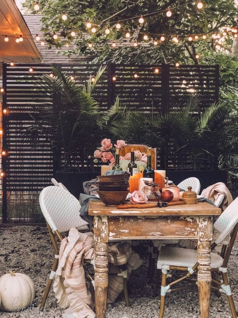 Thanksgiving table centerpiece on an outdoor table under string lights with moody colors and cozy knits