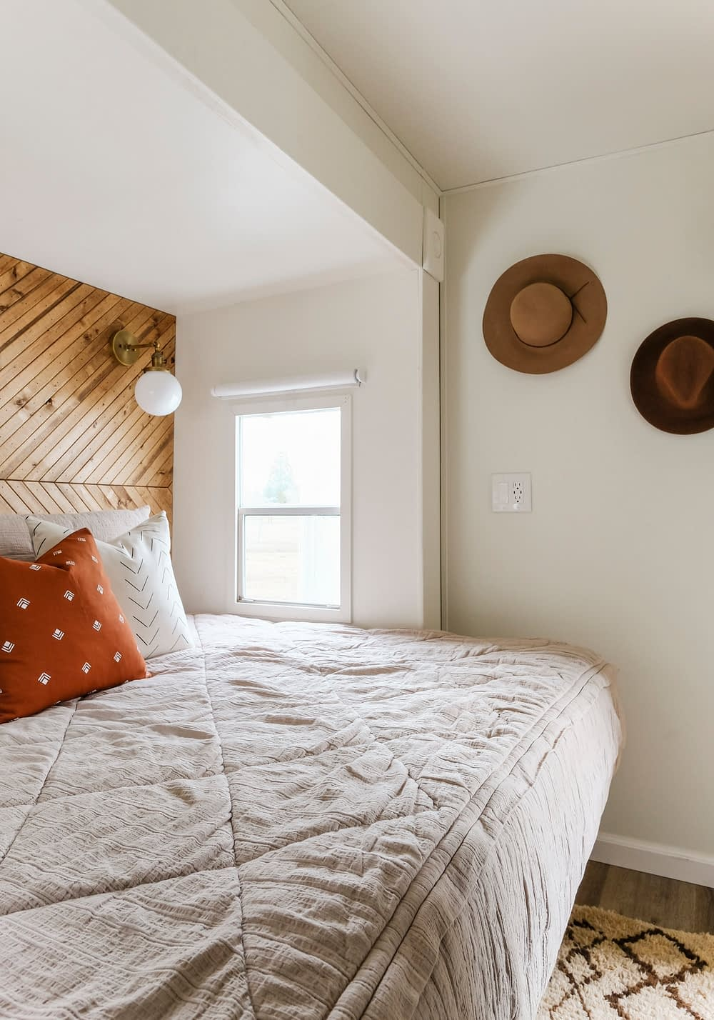 RV bed with zippered bedding and hats on the wall