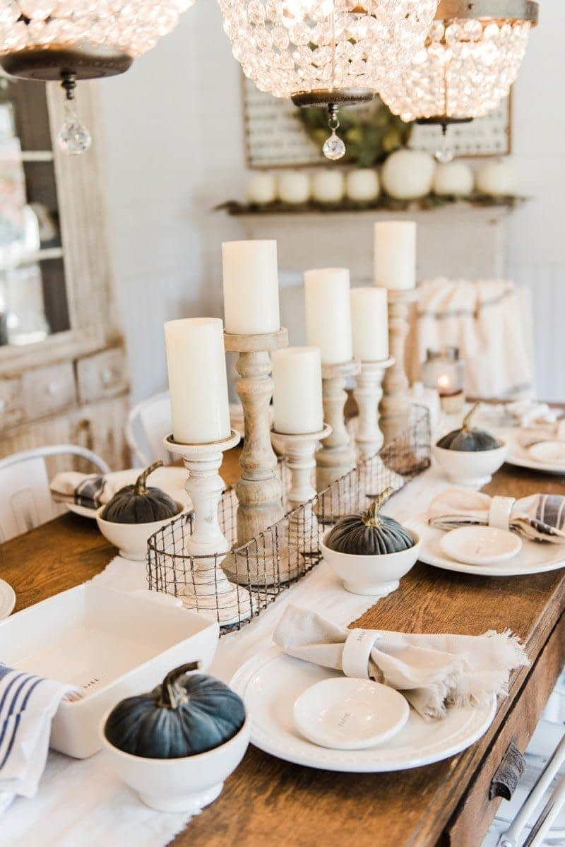 Thanksgiving table centerpieces using wood candlesticks, chunky white candles and a wire crate