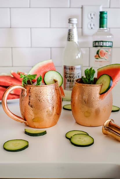 Two copper mugs with ingredients to make cucumber watermelon moscow mules