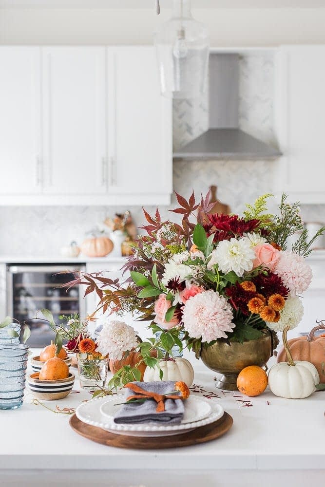 Thanksgiving table centerpieces using a large fall floral arrangement and mini pumpkins