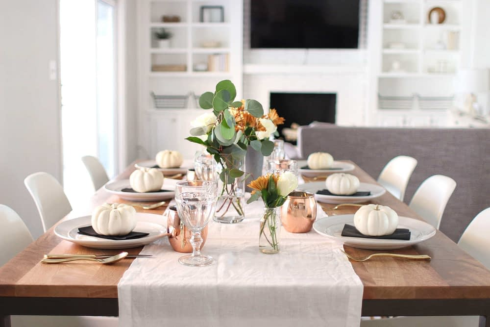 Thanksgiving table centerpieces with white mini pumpkins, a natural table runner and copper mugs