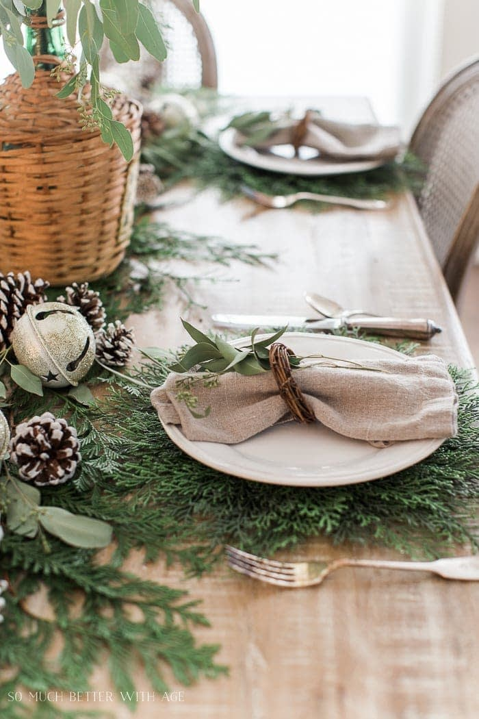 Christmas table setting with cedar chargers and mini wreath napkin rings