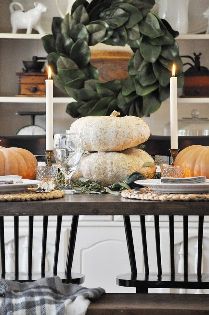 Thanksgiving table centerpieces with stacked white pumpkins in between two tall candlesticks