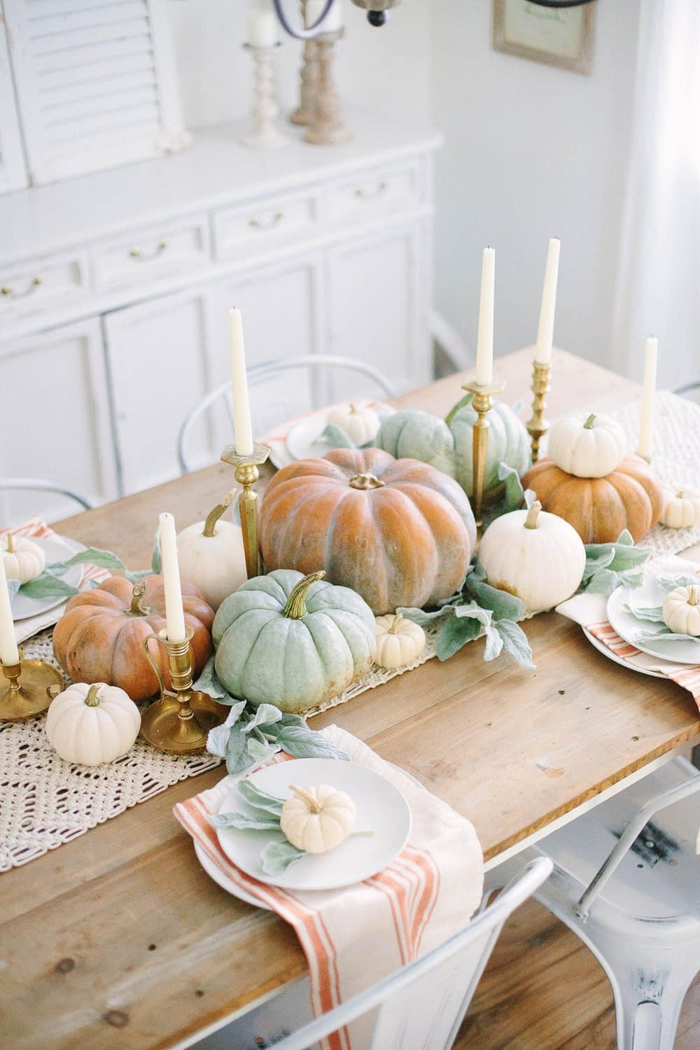 Thanksgiving table centerpieces with pastel colored pumpkins and vintage brass candlesticks
