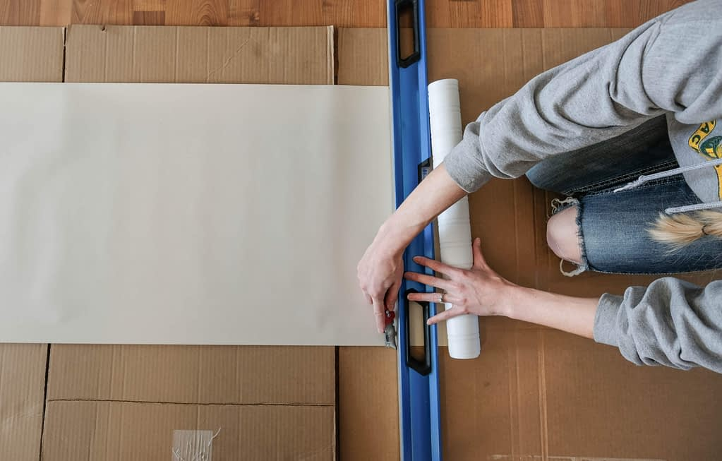 Overhead view of someone using a level and boxcutter to cut a strip of beadboard wallpaper