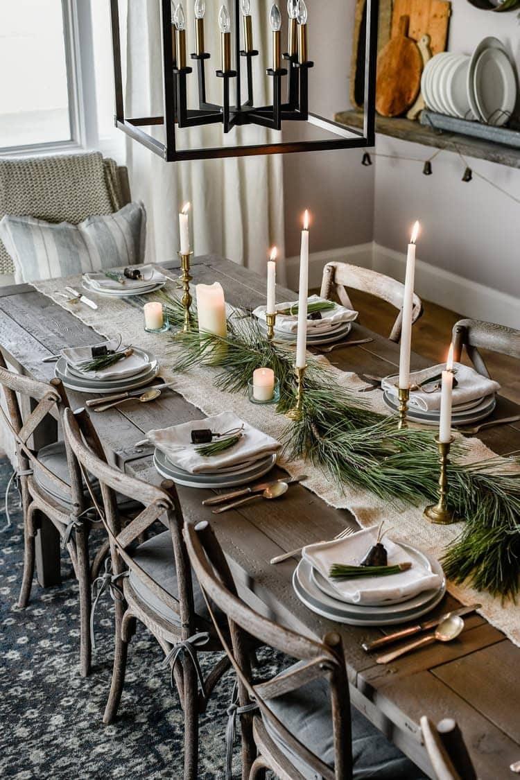 Farmhouse Christmas table centerpiece with jute runner, garland and brass candlesticks