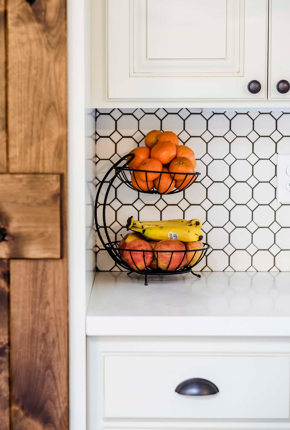 Black stacked fruit basket with oranges and bananas against white penny tile backsplash