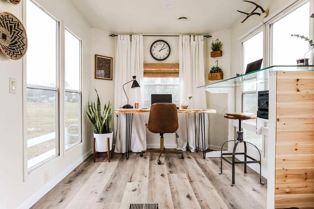 Home office inspiration with white curtains, wood desks and two workstations
