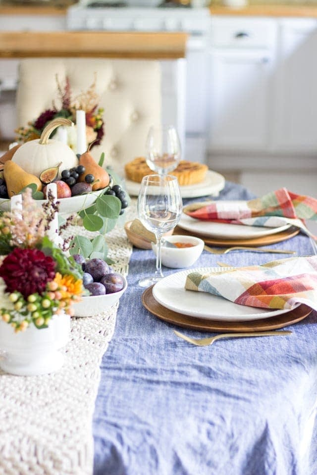 Thanksgiving table centerpieces with pumpkins and fruit and plaid napkins