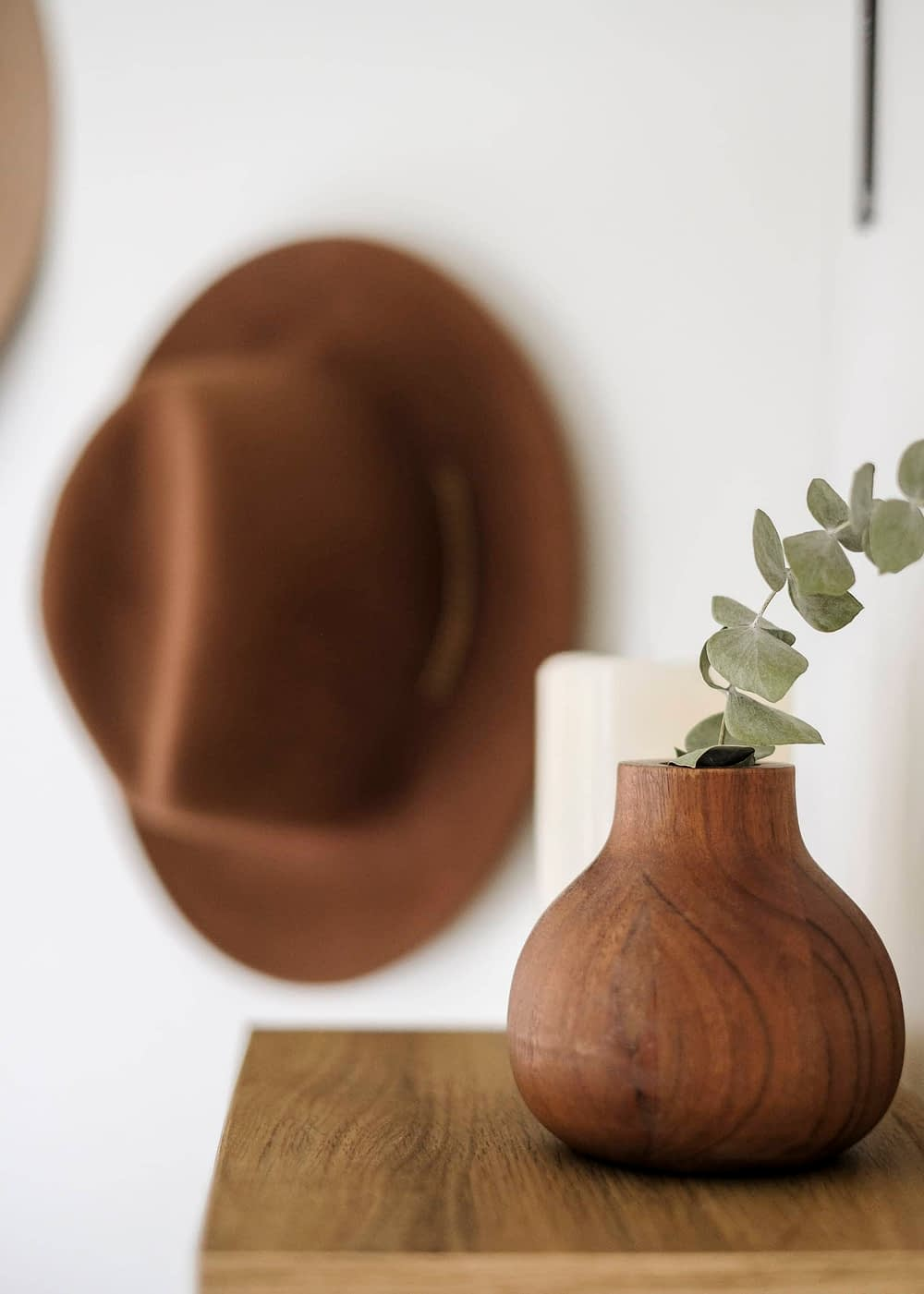 Small wood vase with eucalyptus in it