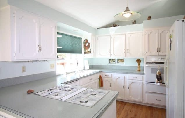country kitchen on a budget with white cabinets and window over sink