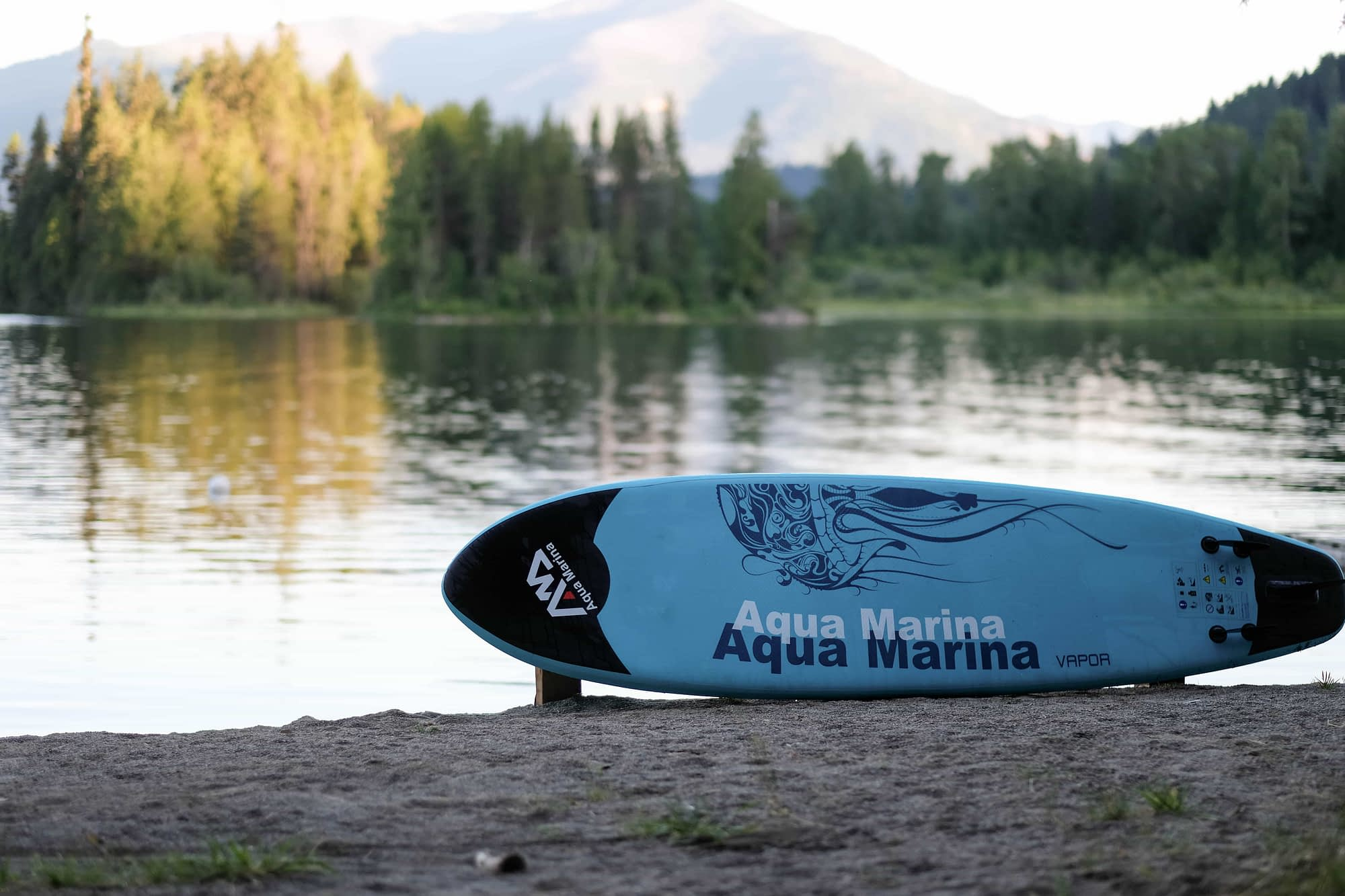 aqua marina VAPOR SUP inflatable SUP sitting on the beach in front of a lake