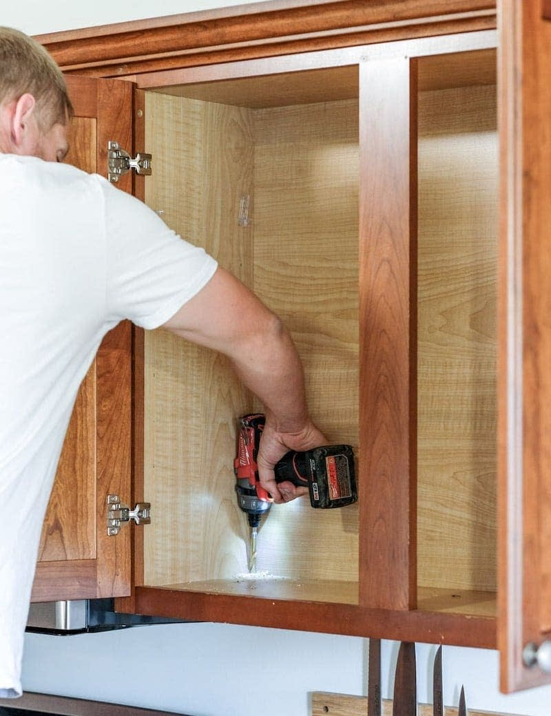 using a Milwaukee drill to install cabinet lights