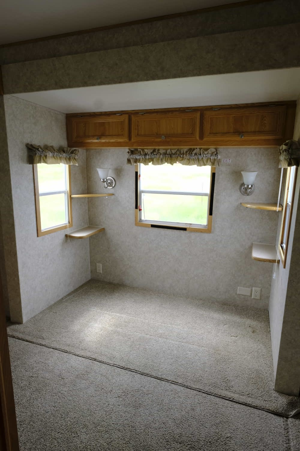 Before photo of a 2005 Damon Bayridge park model RV bedroom with carpet and overhead cabinets