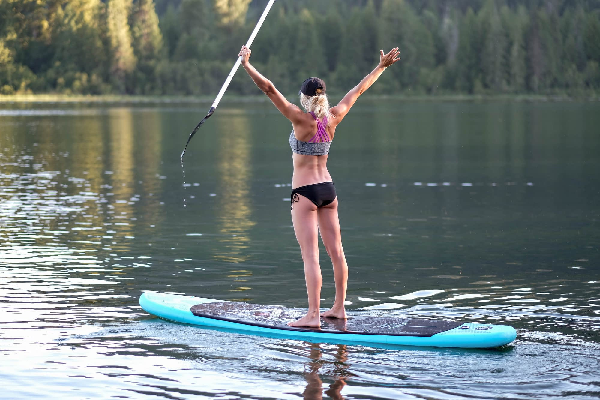 Blond girl standing on inflatable SUP in the middle of a lake with arms raised