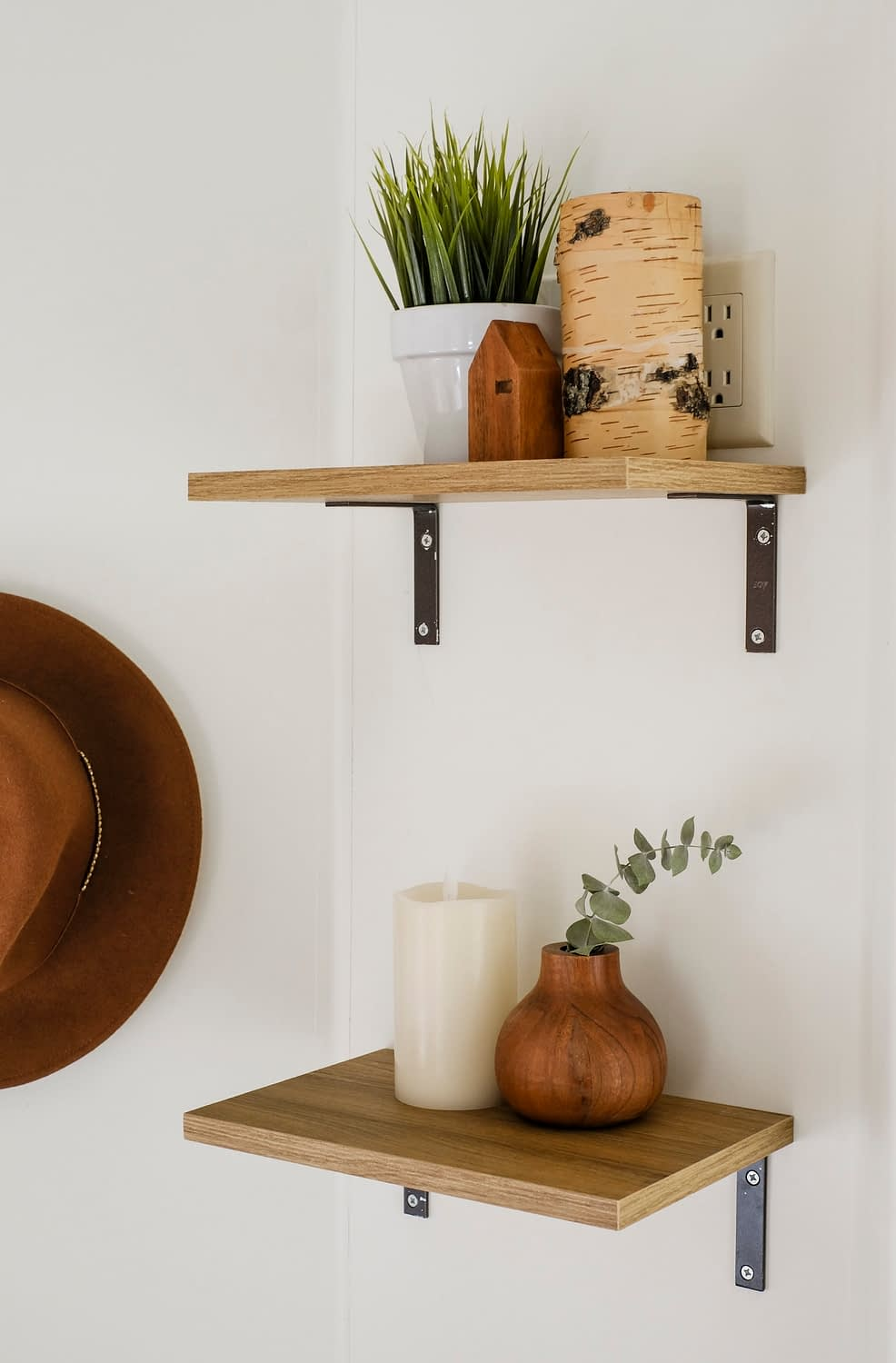 Two open shelves with candles and greenery on top