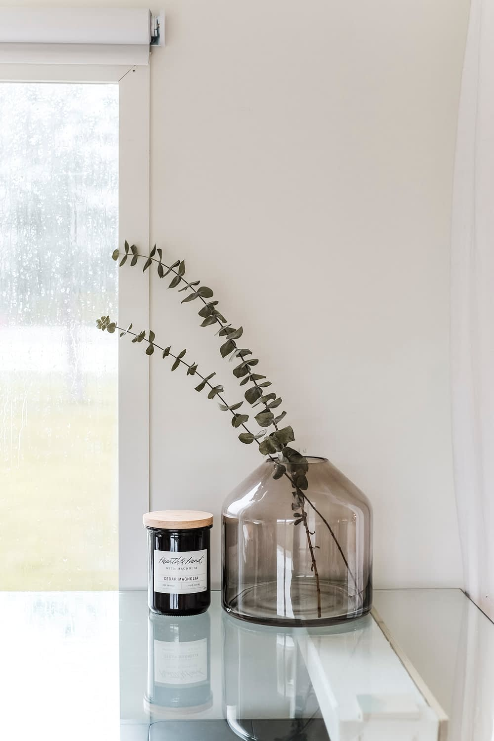 A glass vase with dried eucalyptus next to a candle on top of a glass desktop