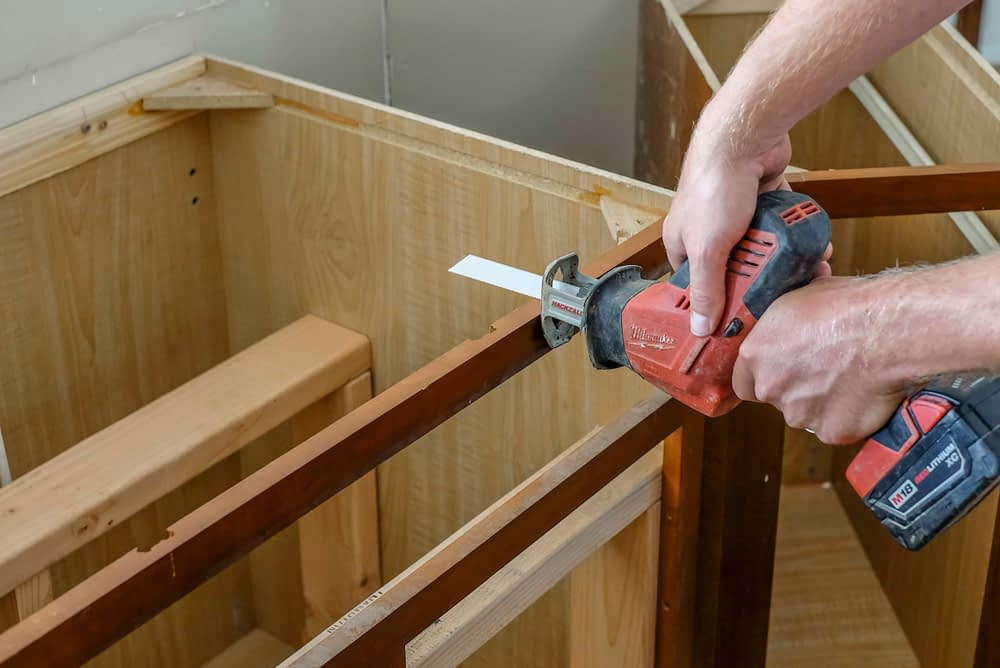 Cutting a cabinet with a sawsall starting to cut into cabinets to make room for farmhosue sink