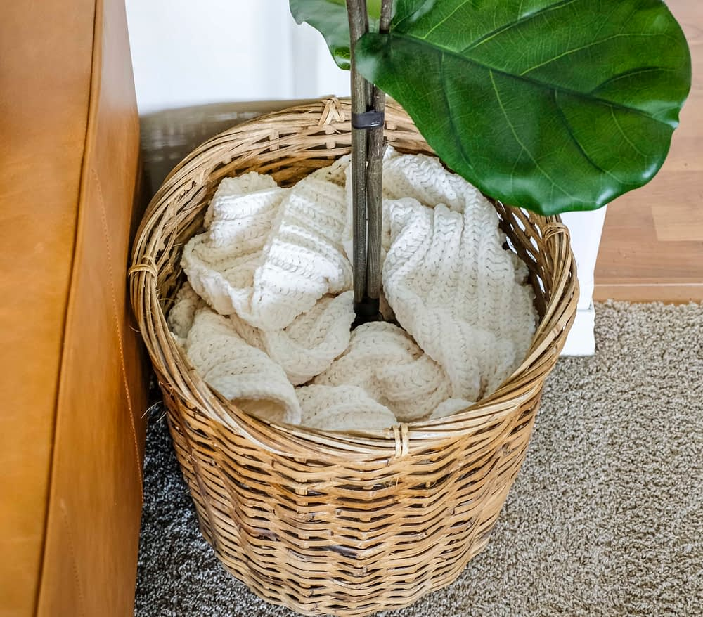 faux fiddle leaf fig tree sitting in a basket with a blanket covering