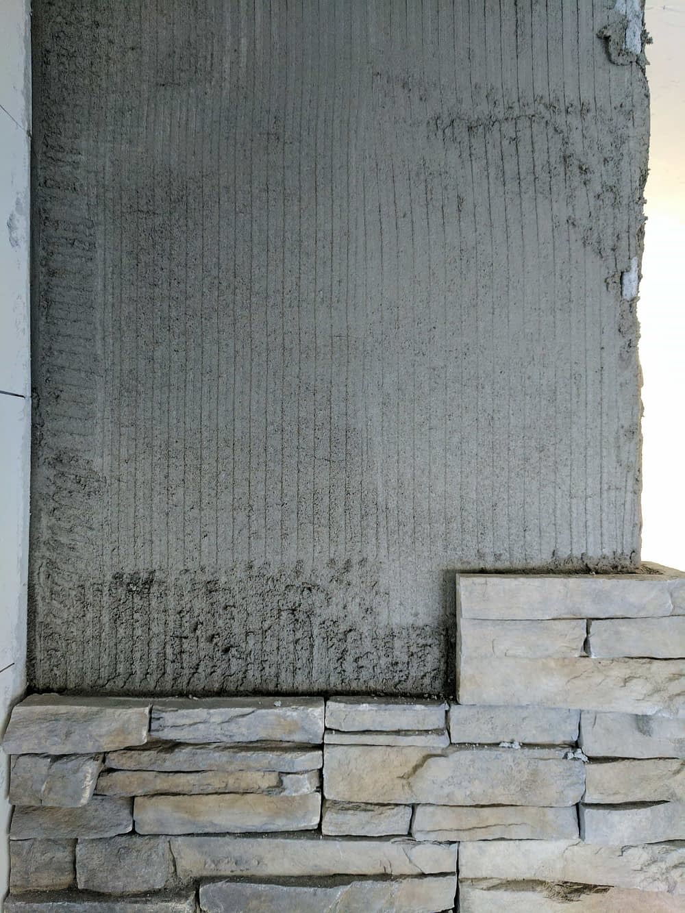 Installing stacked stone veneer on a fireplace
