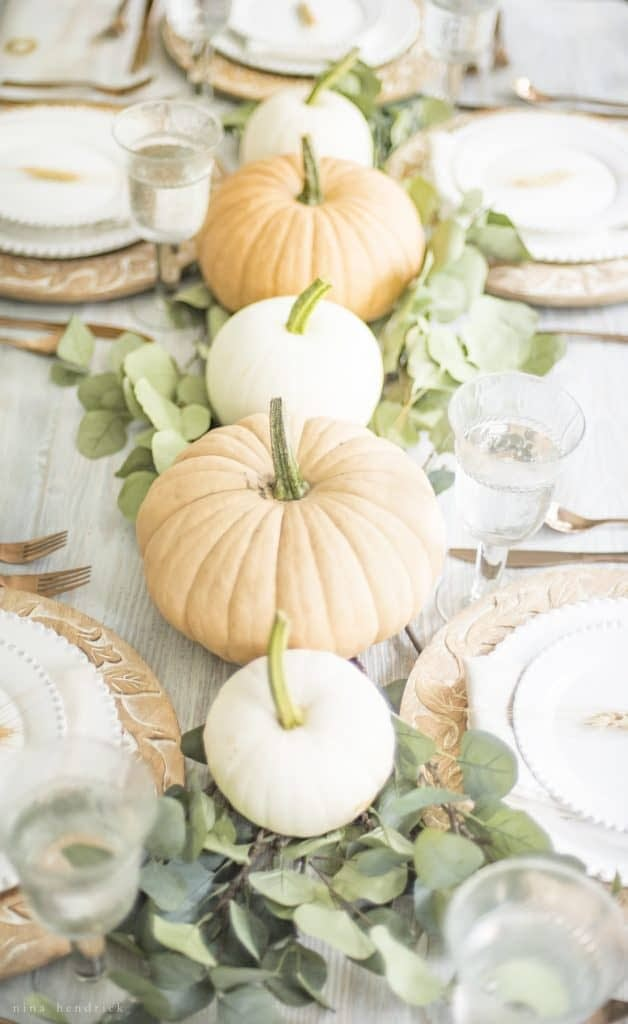 Thanksgiving table centerpieces with alternating orange and white pumpkins on a eucalyptus runner