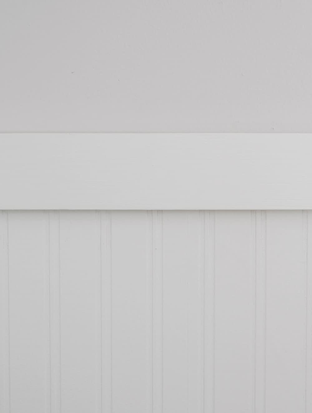Closeup of white trim separating a light grey wall and white beadboard wallpaper