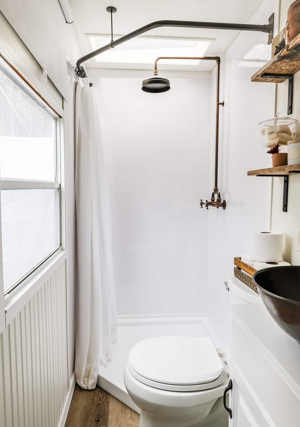 RV bathroom remodel with a bathroom shower combo, open shelving and a vessel sink