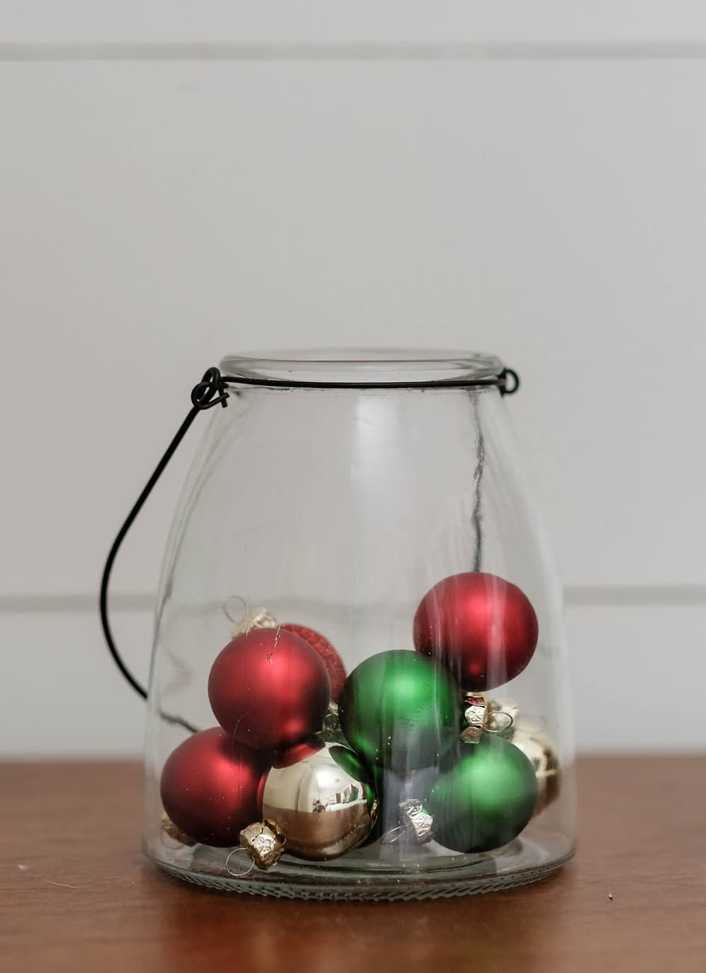 Christmas decor ideas using a glass lantern filled with mini ornaments
