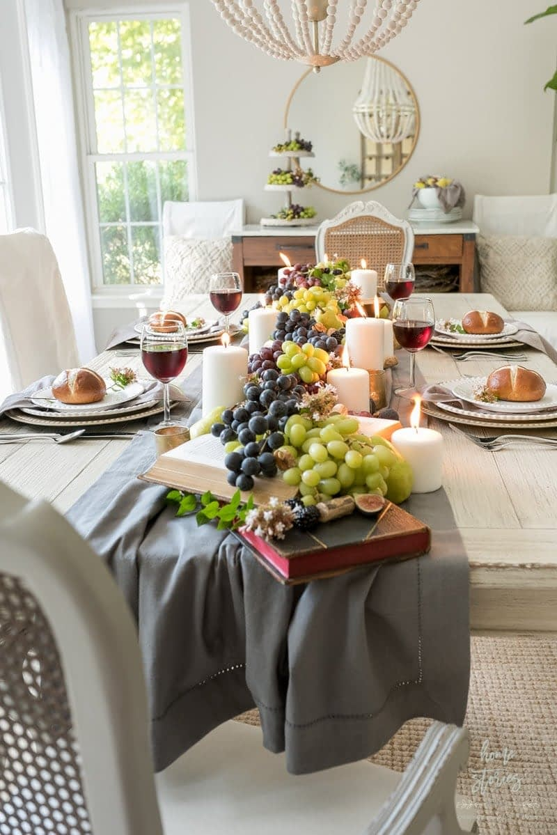 Thanksgiving table centerpieces with a grey runner, grapes and candles