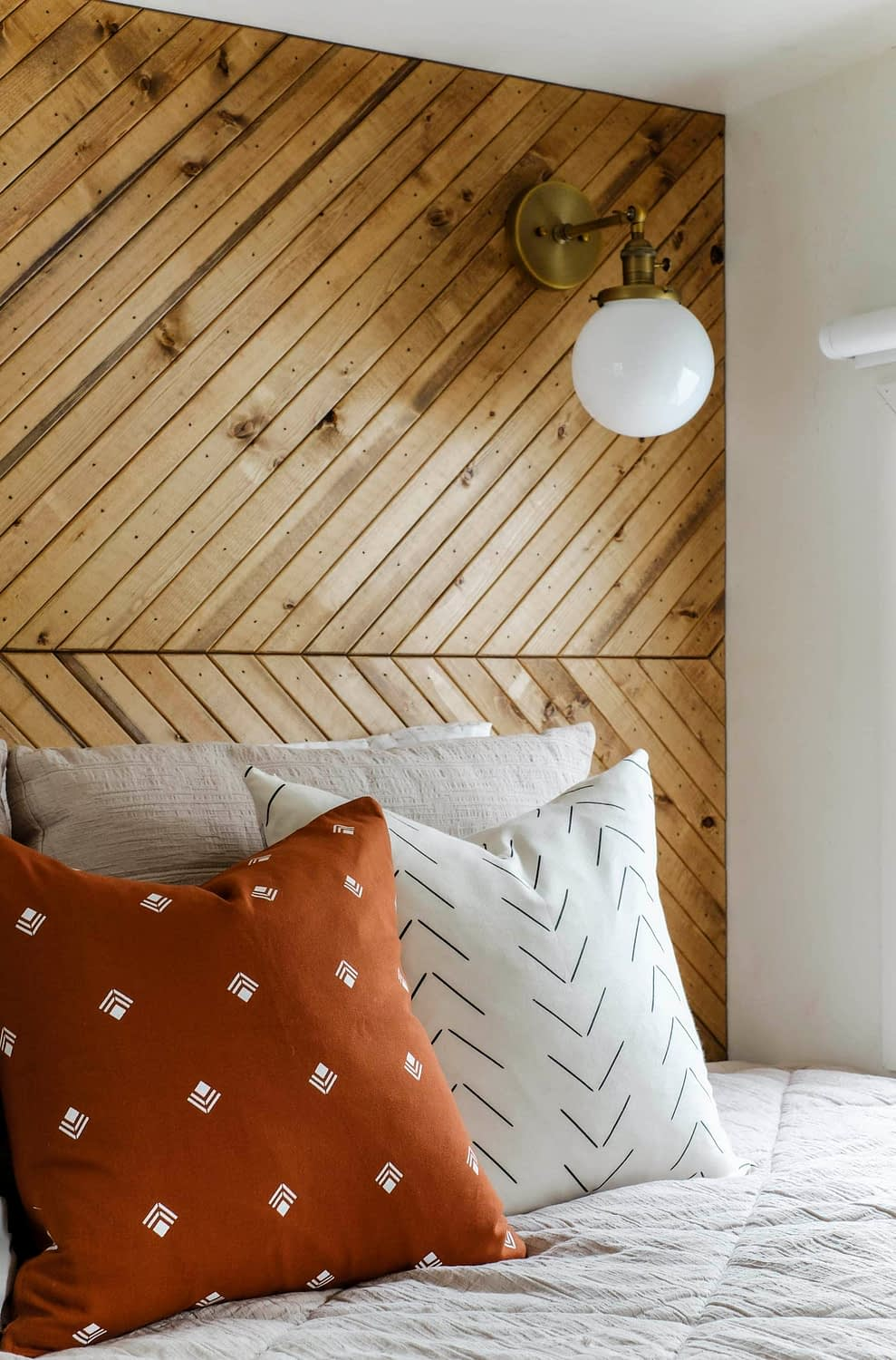 Closeup of geometric pillow covers in front of a wood accent wall