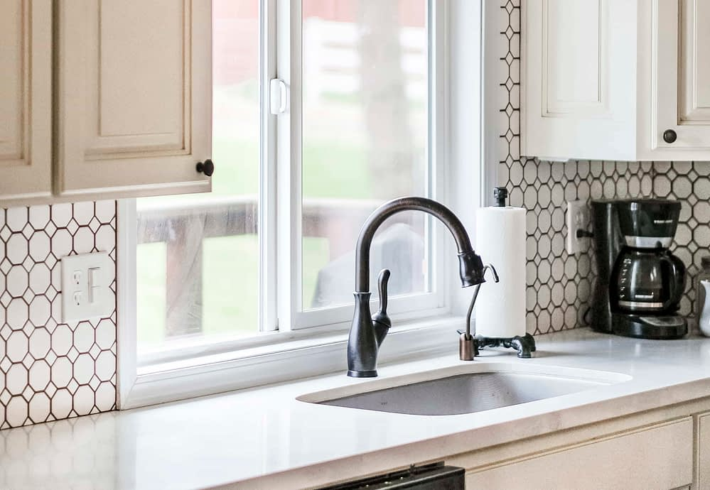 Farmhouse undermount stainless steel sink with goose neck faucet in front of a window