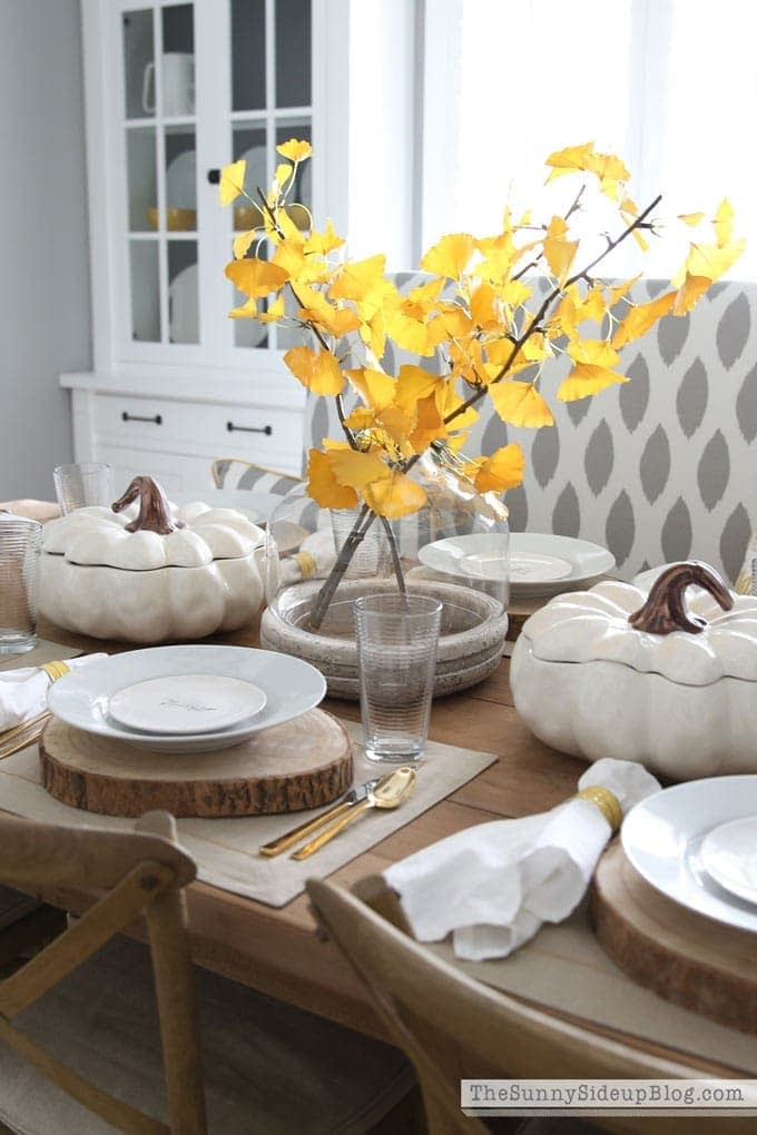 Thanksgiving table centerpieces with bright yellow leaves and white pumpkin casserole dishes