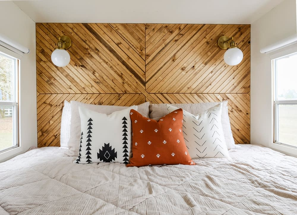 RV bed inside a popout with a wood plank accent wall
