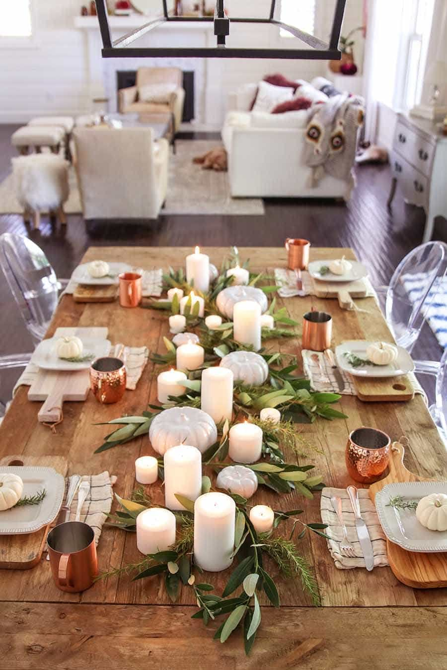 Thanksgiving table centerpieces with lots of candles and copper mugs