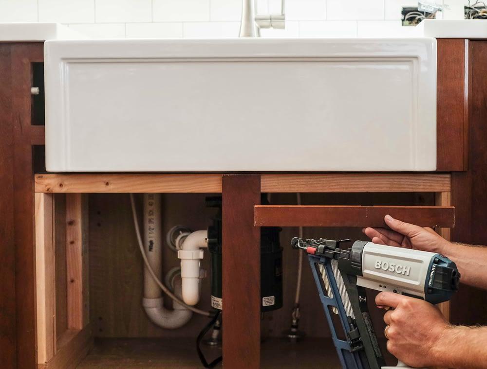 Nail gun installing cabinet trim piece under farmhouse sink
