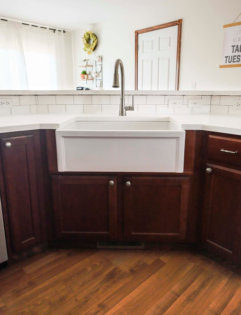 Kitchen with white countertops and wood cabinets with a farmhouse sink