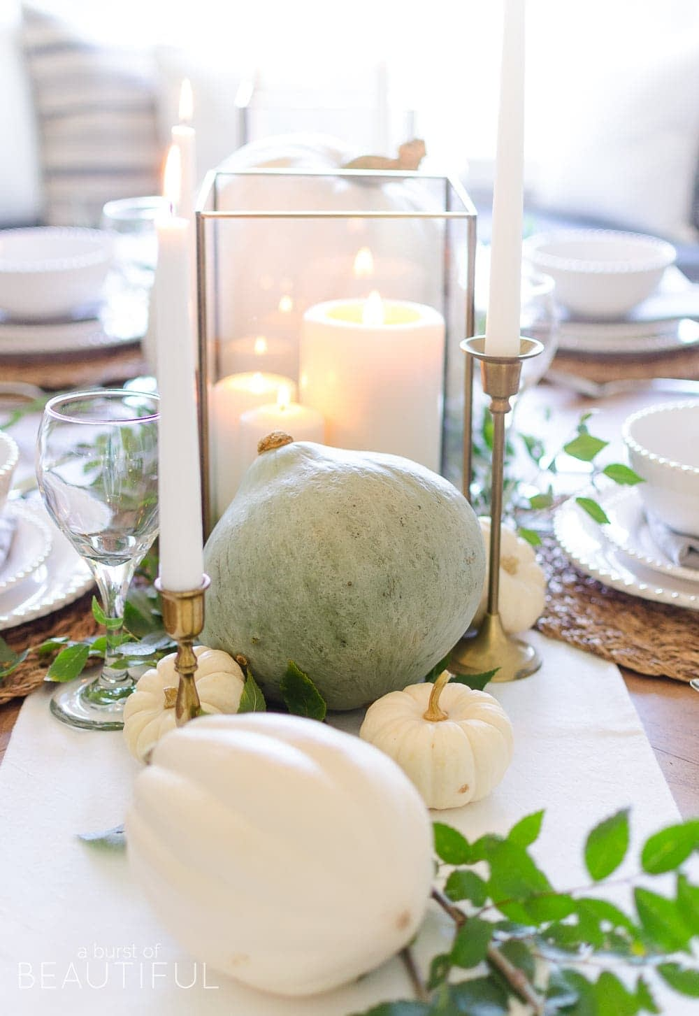 Thanksgiving table centerpieces with neutral colored pumpkins and white candles