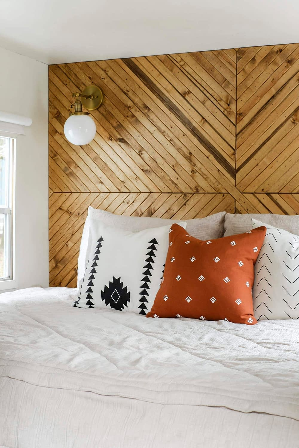 RV bedding with throw pillows and a wood accent wall headboard