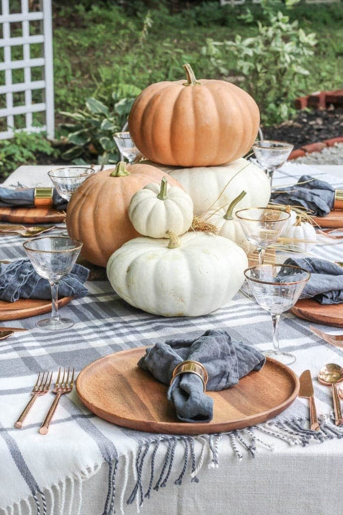 Thanksgiving table centerpieces with plaid tablecloth and large pumpkins next to wood chargers
