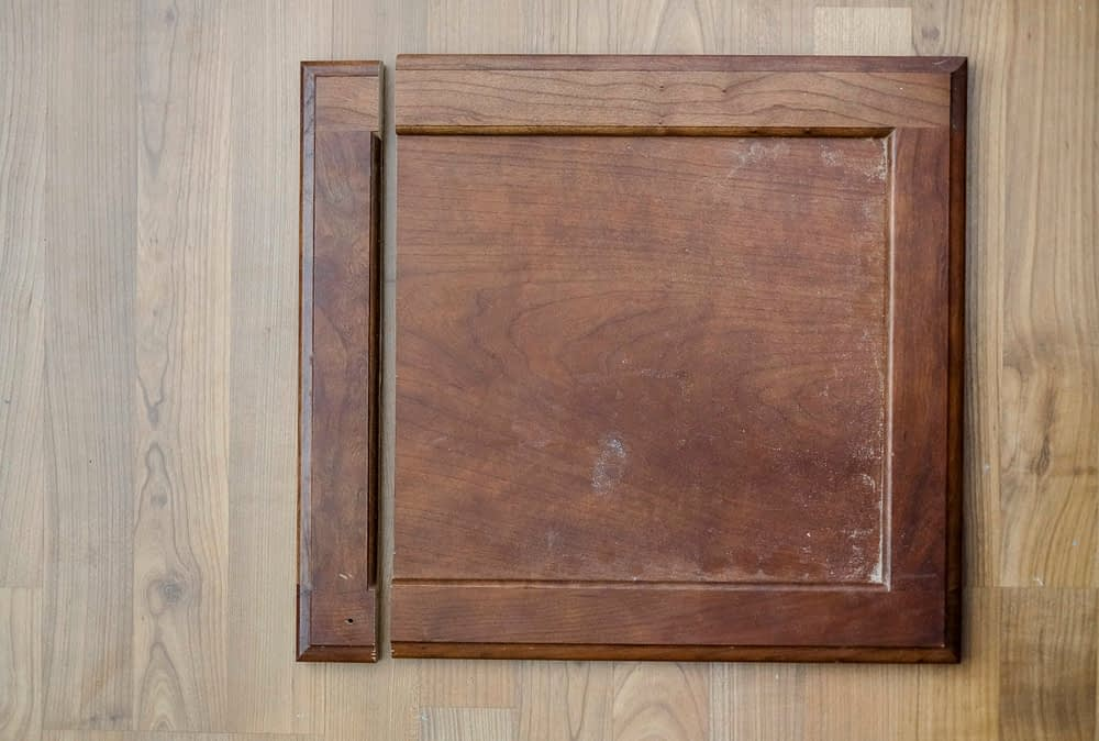 Cabinet door on ground with middle section removed to make it shorter for under an apron front farmhouse sink