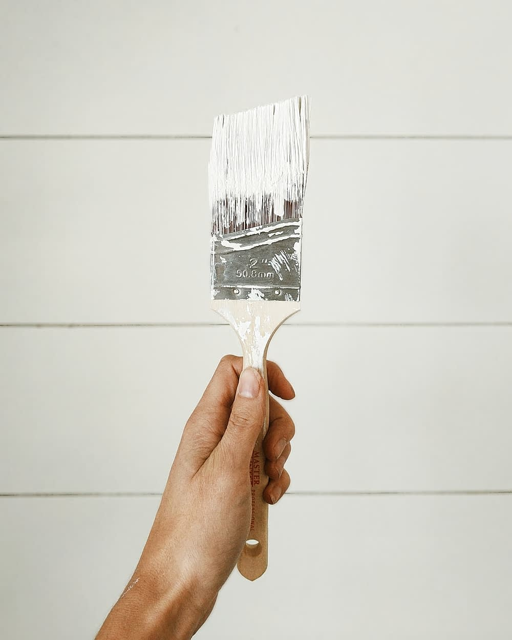 a hand holding a paint brush with white paint on it