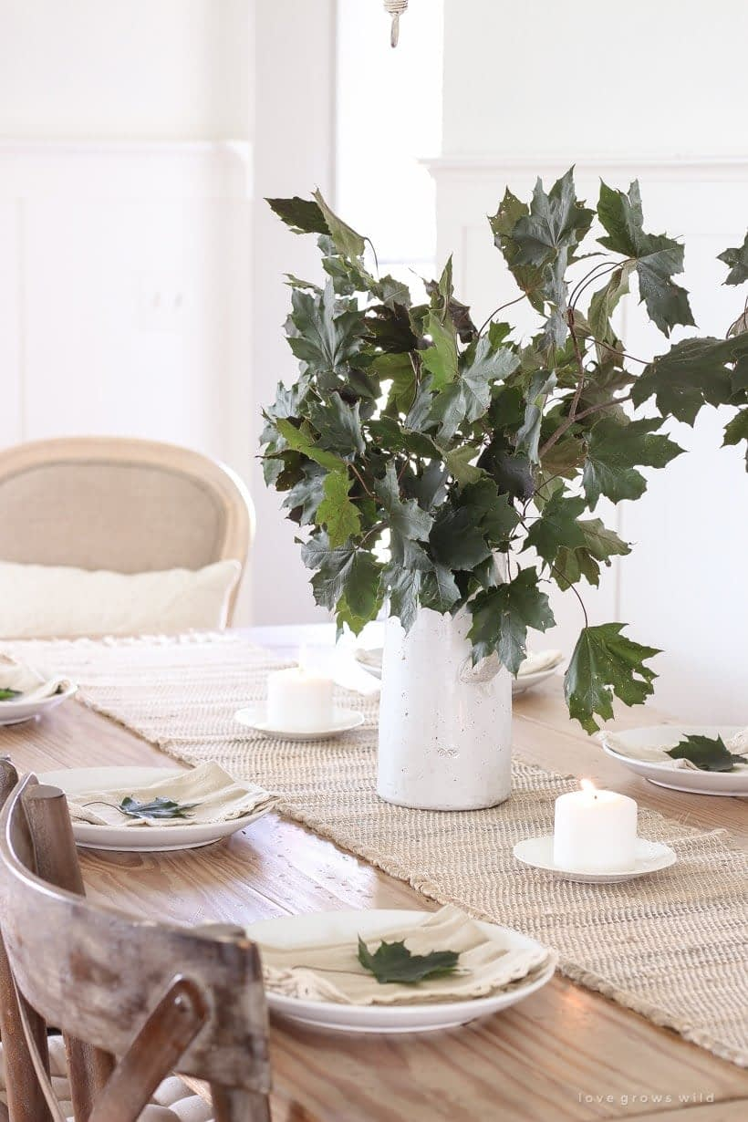 Thanksgiving table centerpieces with a large white pitcher filled with stems with large green leaves on a jute runner