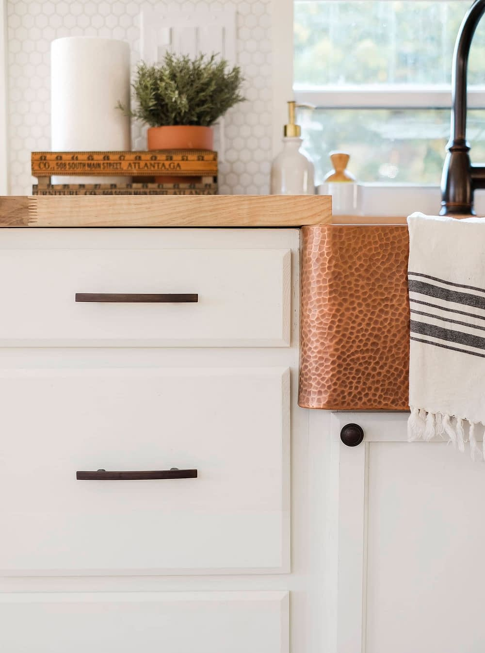 Closeup of cabinet hardware and copper sink