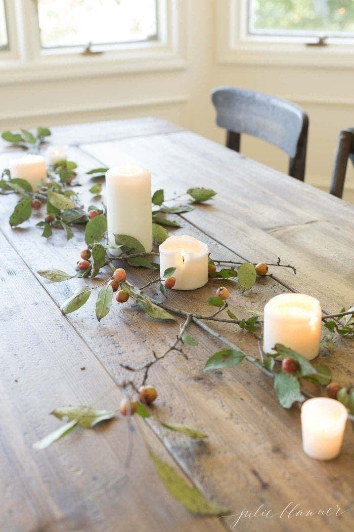 Thanksgiving table centerpieces using a simple runner made from branches and a few candles