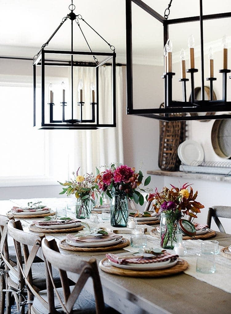 Thanksgiving table centerpieces with three blue vases filled with fall florals and eight place settings