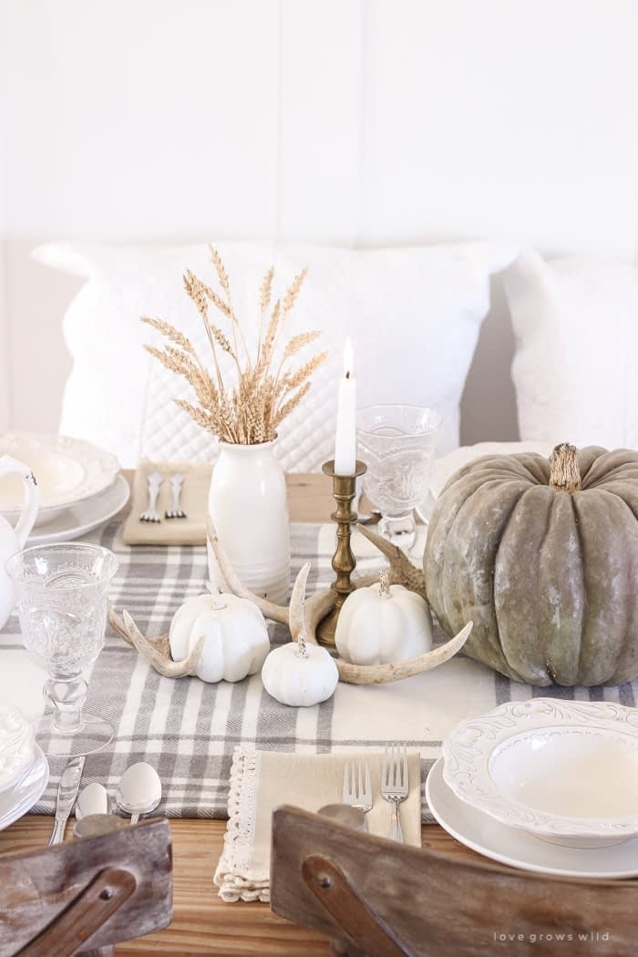 Thanksgiving table centerpieces with neutral colors using wheat stocks antlers and whit pumpkins