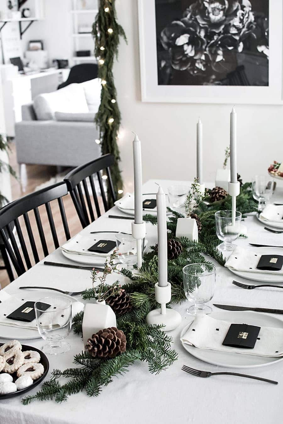 Black and white christmas table decorations using candles and green garland