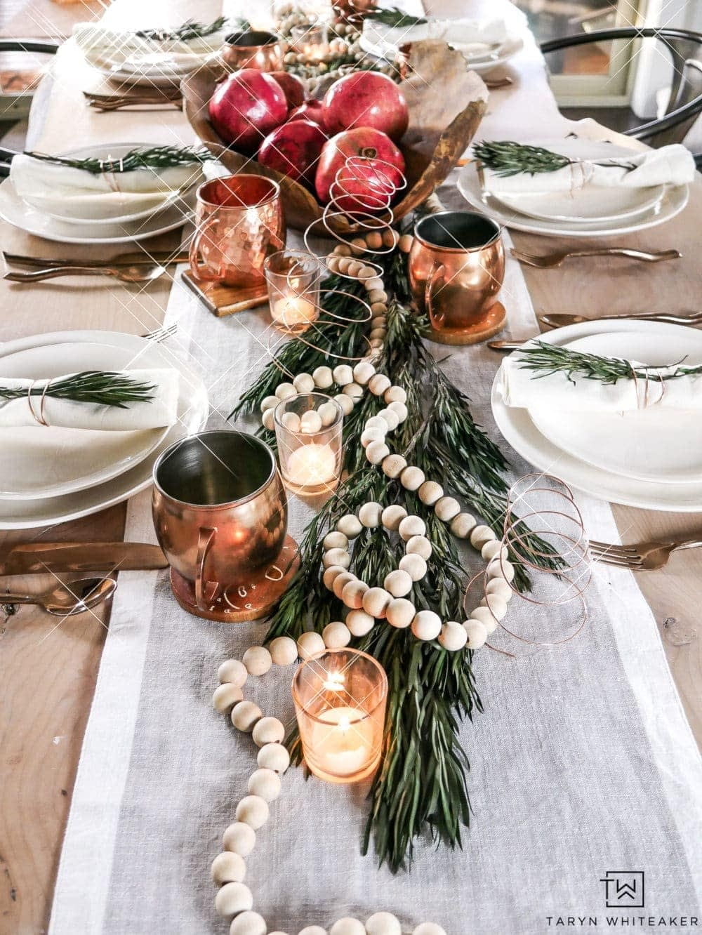 Elegant Christmas table centerpiece with wood bead garland, votive candles and copper mugs